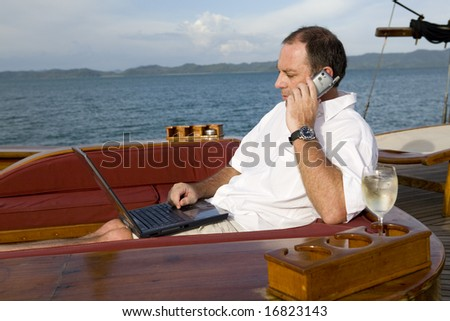 Handsome man on deck of yacht with mobile phone and laptop - stock photo