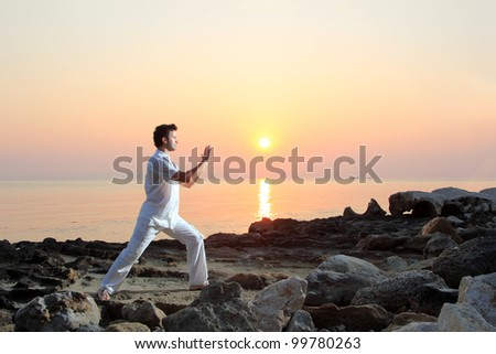 Handsome man on the beach meditating at sunrise / sunset