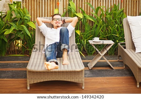 Handsome man on the lounger in the garden - stock photo
