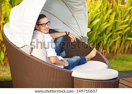 Handsome man on the outdoor bed in the garden of house