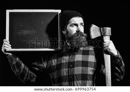 Handsome man or lumberjack, bearded hipster, with beard and moustache in red checkered shirt with axe and empty chalkboard or board isolated on black background, copy space