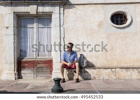 Handsome man. Outdoor male portrait. Middle-aged man sitting near ancient european house against obsolete wall, summer outdoor portrait, image toned.