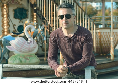 Handsome man over park with carousel. Outdoor male portrait.  - stock photo