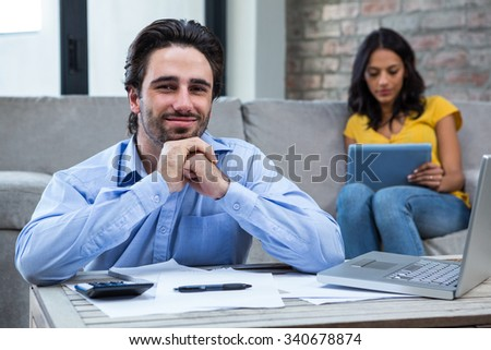 Handsome man paying bills in living room and smiling at the camera - stock photo