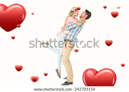 Handsome man picking up and hugging his girlfriend against hearts - stock photo