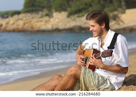 Handsome man playing classic guitar sitting on the beach in vacations - stock photo