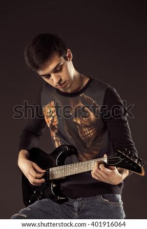 Handsome man playing electro guitar, studio shot - stock photo