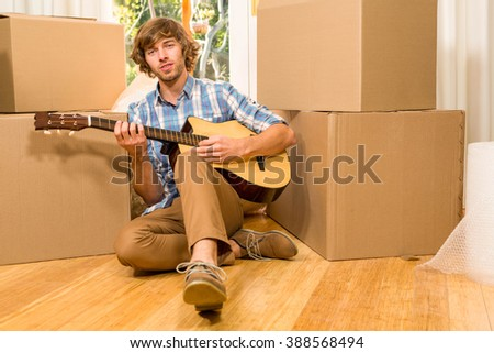 Handsome man playing guitar with moving boxes in his new house
