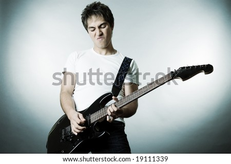 handsome man playing on the guitar. studio shot over grey background - stock photo