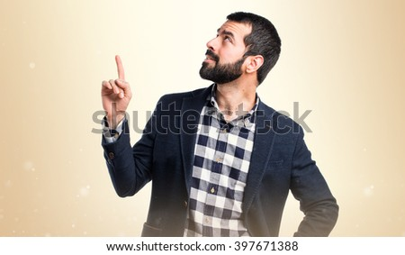Handsome man pointing up over ocher background - stock photo