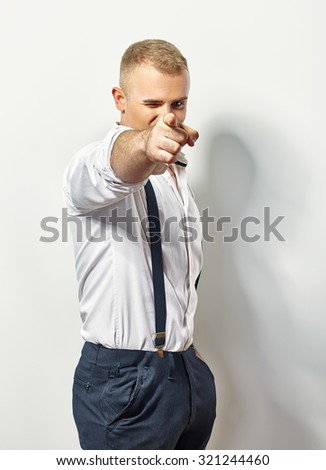 Handsome man points his finger at you on white