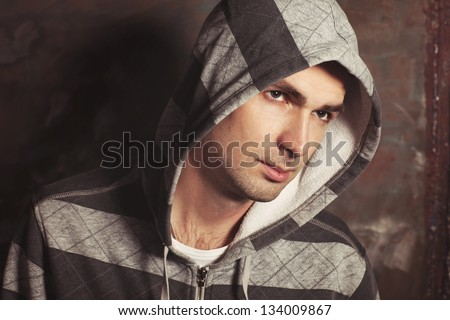 Handsome man portrait on graffiti grunge wall at street in casual sweater. Hip hop dancer angry guy in jacket. Hooligan male mob. Male Fashion. brutal sexy stylish guy model Rapper or rnd singer