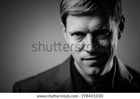 Handsome man portrait with an evil smirk - stock photo