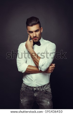 Handsome man posing in studio on dark background - stock photo