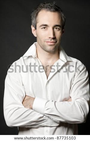 Handsome man posing in white shirt on dark background in studio. - stock photo
