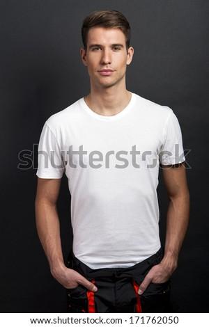 Handsome man posing in white tshirt on dark background in studio. - stock photo