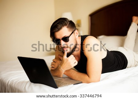 Handsome man posing outdoor at  hotel and working on black laptop with case,young travel businessman working hard,stylish man with perfect muss hairstyle,bearded,muscular body,man's black sunglasses - stock photo