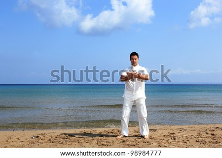 Handsome man practicing thai chi on the beach in the summertime