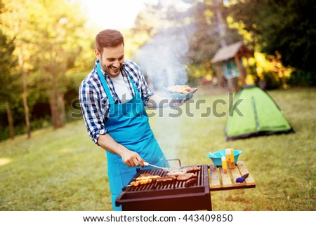 Handsome man preparing barbecue for friends - stock photo