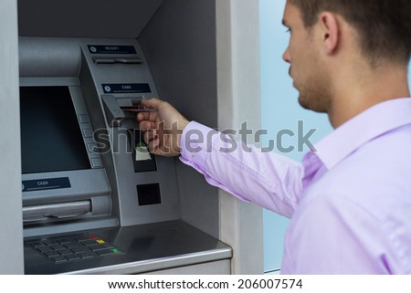 Handsome man put his credit card at the ATM  - stock photo