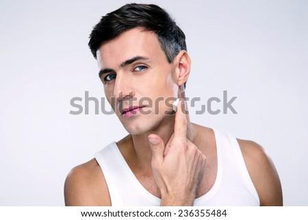 Handsome man putting cream on a face  - stock photo