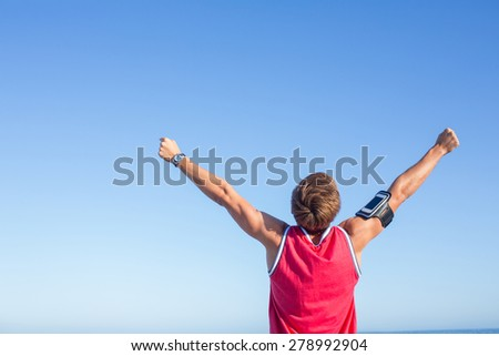 Handsome man raising arms at the beach - stock photo