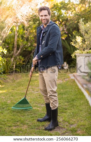 Handsome man raking in his garden on a sunny day