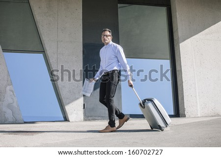 Handsome man reading a newspaper on a grunge background/  Businessman walking with bag to the convention.