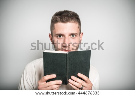 handsome man reading a notebook, isolated on a gray background