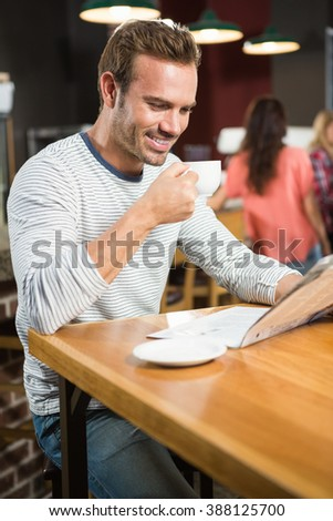 Handsome man reading newspaper and having a coffee in a pub