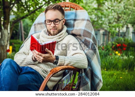 Handsome man relax in rocking-chair & reading red book in summer garden.