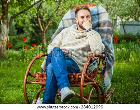 Handsome man relax in rocking-chair with cup of tea in summer garden.  - stock photo