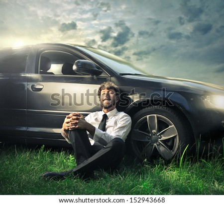 handsome man relaxing leaning against his car sitting on the grass - stock photo