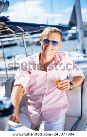 Handsome man relaxing on a sailing boat - stock photo