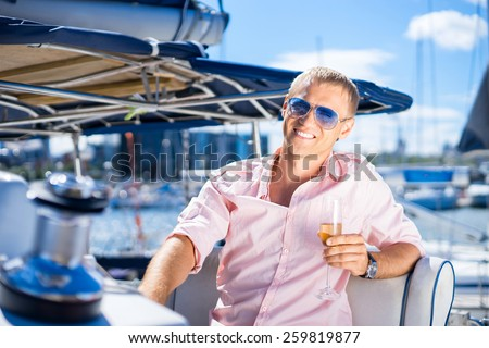 Handsome man relaxing on a sailing boat
