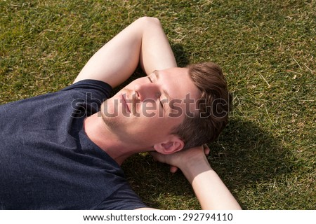 Handsome man relaxing on green grass field - stock photo