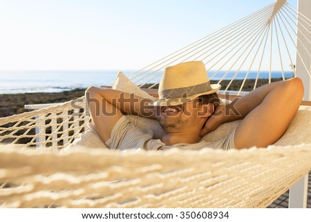 Handsome man resting in the hammock - stock photo
