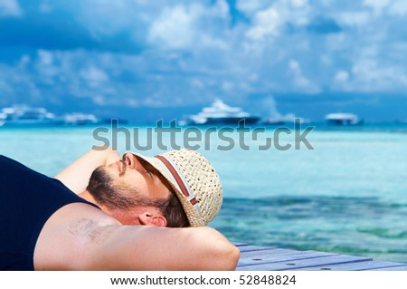 Handsome man resting near water at Maldives - stock photo