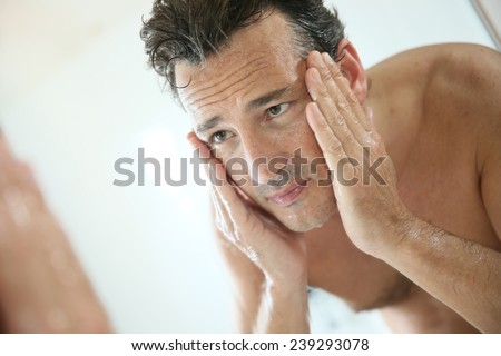 Handsome man rinsing face after shaving - stock photo