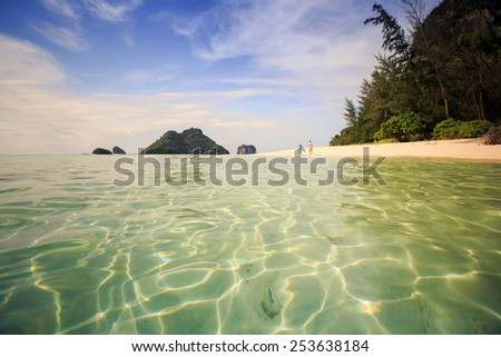 handsome man run with his beautiful blonde wife in elegant dress on island beach with green mountain on background - stock photo