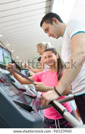 handsome man running on  treadmill , personal trainer compare result of training