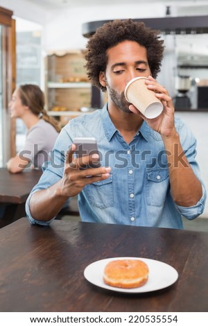 Handsome man sending a text drinking coffee at the coffee shop - stock photo