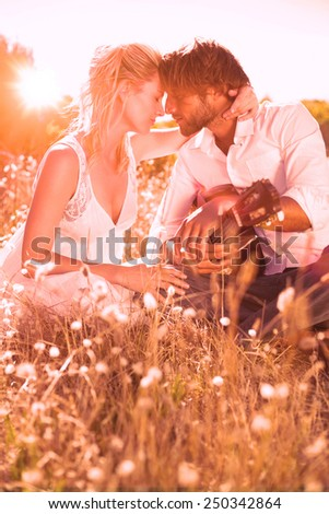 Handsome man serenading his girlfriend with guitar on a sunny day - stock photo