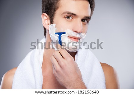 Handsome man shaving. Handsome shirtless young man shaving his face and looking at camera while standing isolated on grey background - stock photo