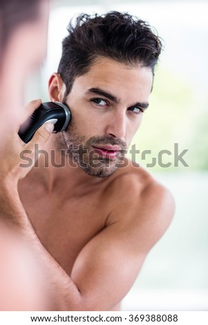 Handsome man shaving in the mirror in the bathroom - stock photo