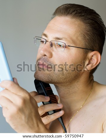 Handsome man shaving with electric razor, looking into mirror