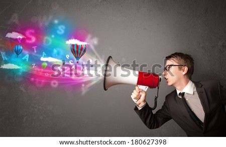 Handsome man shouting into megaphone and abstract text and balloons come out - stock photo