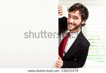 Handsome man showing a blank board