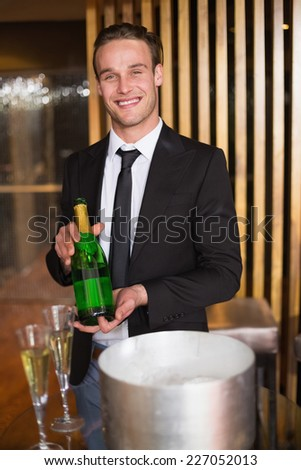Handsome man showing champagne bottle at the bar