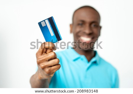 Handsome man showing his debit card to camera - stock photo